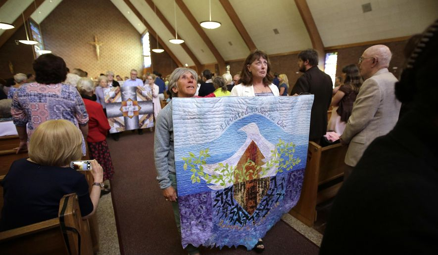 Parishioners carry quilts made to commemorate a vigil at the St. Frances X. Cabrini Church at the conclusion of a planned final service at the church, Sunday, May 29, 2016, in Scituate, Mass. For more than 11 years, a core group of about 100 die-hard parishioners at the church have kept their parish open by maintaining an around-the-clock vigil in protest of a decision by the Roman Catholic Archdiocese of Boston to close it following the clergy sex abuse crisis. (AP Photo/Steven Senne)