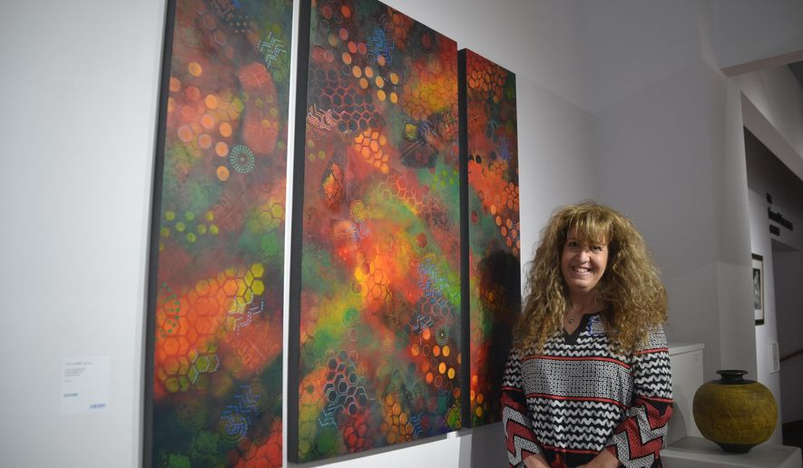 """In this May 22, 2016, photo, Lauri Reidmiller, of Shady Spring, W.Va., poses with her acrylic painting """"Cut So Deep,"""" which was the winner of Best of Show at the West Virginia Allied Artists 70th Annual Exhibit, at the Parkersburg Art Center, in Parkersburg, W.Va. (Brett Dunlap/News and Sentinel via AP) MANDATORY CREDIT"""