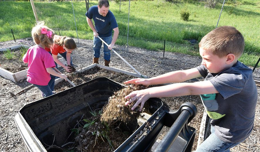 ADVANCE FOR SUNDAY MAY 29 AND THEREAFTER - In a Wednesday, May 18, 2016 photo, Ben Bittinger, 8, tosses old leaves and mulch into a bin as he and family members, from left, Ella, Ali, and their father, Dan Bittinger, associate pastor of CrossPointe Church, clean up a garden bed, at the west side Sioux City, Iowa, church. The church offers 20 community garden plots and supplies tools, water and seeds. (Tim Hynds/Sioux City Journal via AP)