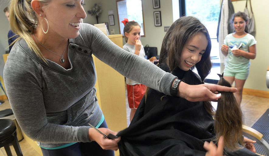 ADVANCE FOR MONDAY MAY 30, 2016, AND THEREAFTER - In this Monday, May 23, 2016 photo stylist Vanessa Davis shows Girl Scout Emerson Sadorra the hair that was just snipped off the young Scout at Allure Styling Salon, in Charleston, W. Va. Several Black Diamond Girl Scout Brownies had their locks cut to donate to Children with Hair Loss. (F. Brian Ferguson/Charleston Gazette-Mail via AP) MANDATORY CREDIT