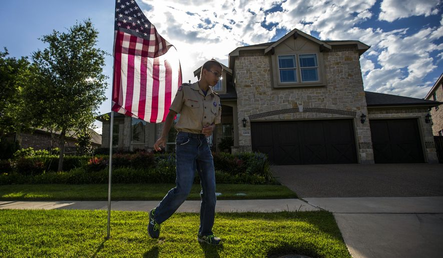 Boy scout Zach Plyler, 13, posts an American flag at a home on Thornberry Drive on Thursday, May 26, 2016, in McKinney, Texas.  The McKinney Sunrise Rotary Club, along with local boy scouts, are posting more than 1,700 flags in area neighborhoods for Memorial Day. (Ashley Landis/The Dallas Morning News via AP)