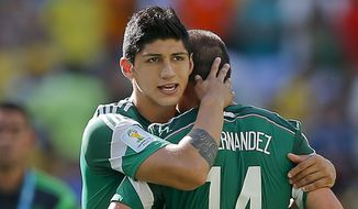 In a June 29, 2014, file photo, Mexico's Alan Pulido consoles teammate Javier Hernandez (14) after the Netherlands defeated Mexico 2-1 during the World Cup round of 16 soccer match between the Netherlands and Mexico at the Arena Castelao in Fortaleza, Brazil. (AP Photo/Eduardo Verdugo, File)