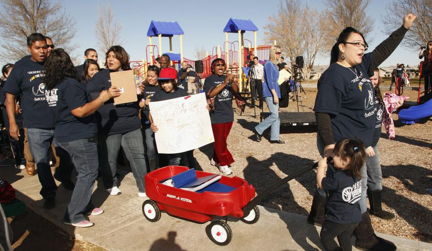 FILE - In this Jan. 12, 2012, file photo, parent Olivia Samaripa, far right, with her daughter Aria, 2, pull a wagon carrying petitions calling for their school to be converted to a charter school in the Mojave Desert town of Adelanto, Calif. More than 100,000 students in the nation's second-largest school district are now enrolled in charters, draining nearly $592 million from the budget in one school year alone. In Los Angeles, school board members are waging a battle to try and regain the public's trust in district schools. (AP Photo/Damian Dovarganes, File)