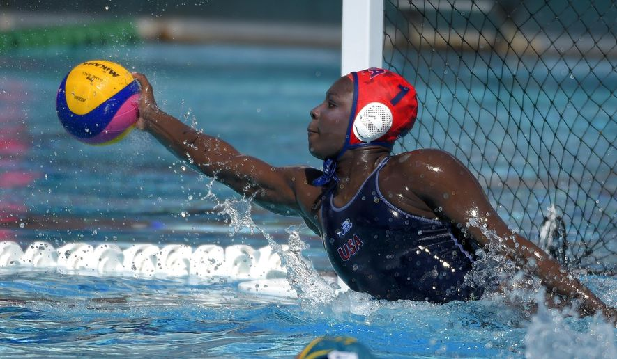 In this May 22, 2016, photo, U.S. goalkeeper Ashleigh Johnson stops a shot during an exhibition water polo match against Australia in Los Angeles. Johnson, a goaltender blessed with jaw-dropping athleticism, is a lock for Rio de Janeiro, putting her on track to become the first black woman to play water polo for the U.S. Olympic team. (AP Photo/Mark J. Terrill)