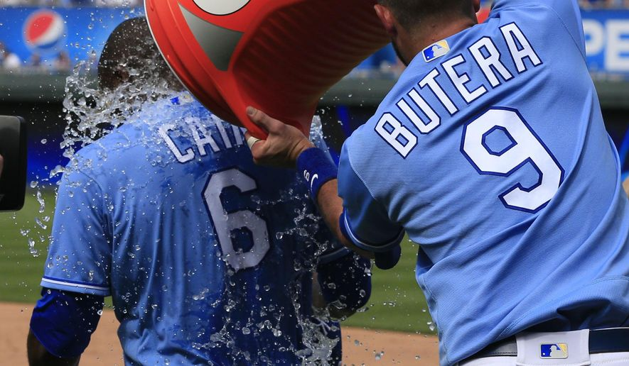 Kansas City Royals' Drew Butera (9) douses teammate Lorenzo Cain (6) following a baseball game against the Chicago White Sox at Kauffman Stadium in Kansas City, Mo., Sunday, May 29, 2016. The Royals defeated the White Sox 5-4. (AP Photo/Orlin Wagner)
