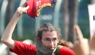 Inflammatory: A protester sets a Donald Trump campaign hat on fire during a rally Friday in San Diego. Polling suggests voters blame the presumptive Republican presidential nominee for violence but blame rioters even more. (San Diego Union-Tribune via Associated Press)