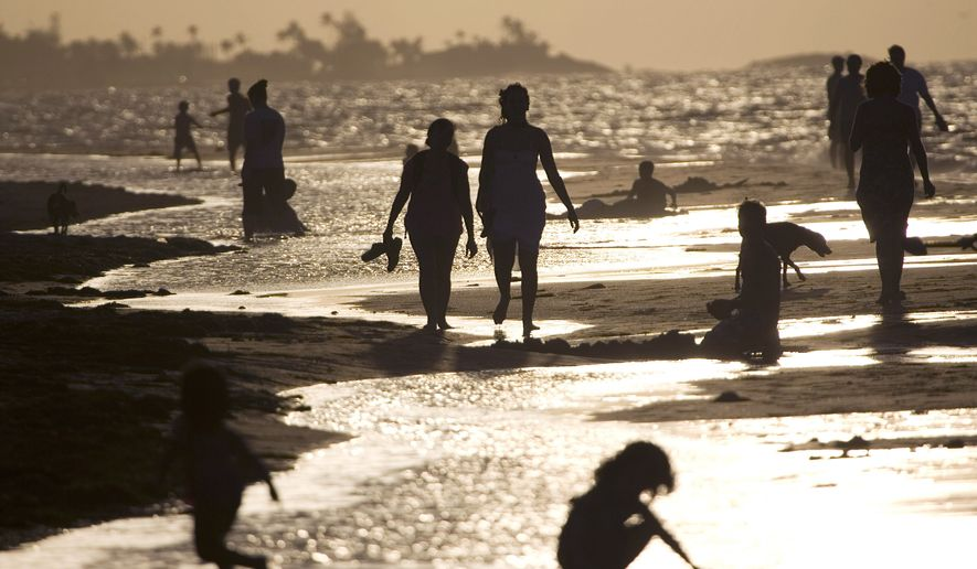 People walk and play on a beach in San Juan, Puerto Rico, on June 12, 2008. People have become increasingly reluctant to travel to an island where the Zika virus has caused one death, infected more than 1,100 people and is linked to the first microcephaly case acquired on U.S. soil. (Associated Press) **FILE**