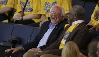 Democratic presidential candidate Sen. Bernie Sanders, I-Vt., left, laughs with actor Danny Glover during Game 7 of the NBA basketball Western Conference finals between the Golden State Warriors and the Oklahoma City Thunder in Oakland, Calif., Monday, May 30, 2016. (AP Photo/Ben Margot)