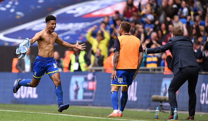 AFC Wimbledon's Lyle Taylor, left, celebrates scoring his side's first goal of the game during their League Two Play-Off Final soccer match against Plymouth Argyle at Wembley Stadium, London, Monday, May 30, 2016. AFC Wimbledon, an English soccer club created in 2002 by disgruntled supporters after their original team was controversially relocated and rebranded, continued its rise up the league pyramid by getting promoted to the third tier on Monday. The south London team beat Plymouth 1-0 in the fourth-tier League Two playoff final at Wembley Stadium. (Andrew Matthews/PA via AP)      UNITED KINGDOM OUT       -      NO SALES      -      NO ARCHIVES