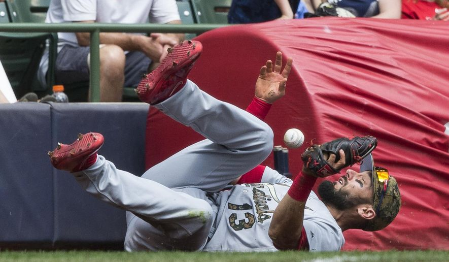 St. Louis Cardinals' Matt Carpenter makes a diving attempt at a foul ball hit by Scooter Gennett during the third inning of a baseball game Monday, May 30, 2016, in Milwaukee. Carpenter was not able to make the catch on the play. (AP Photo/Tom Lynn)