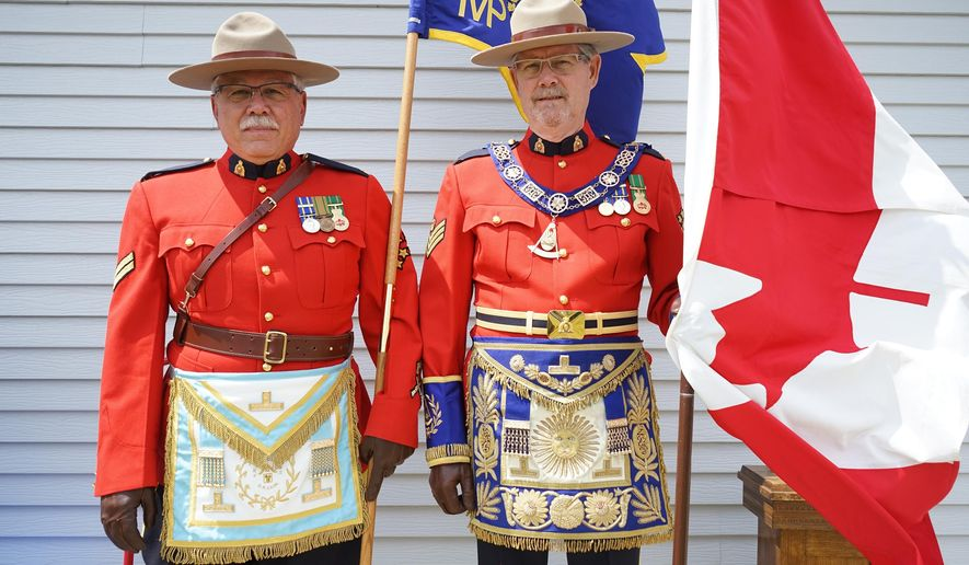 In this Saturday, May 28, 2016 photo, Dave Abel, right, and Bill Betker pose for a photo in Fort Buford, N.D. They are members of the Masons as well as retired Royal Canadian Mounted Police. (Alexa Althoff/Williston Herald via AP) MANDATORY CREDIT