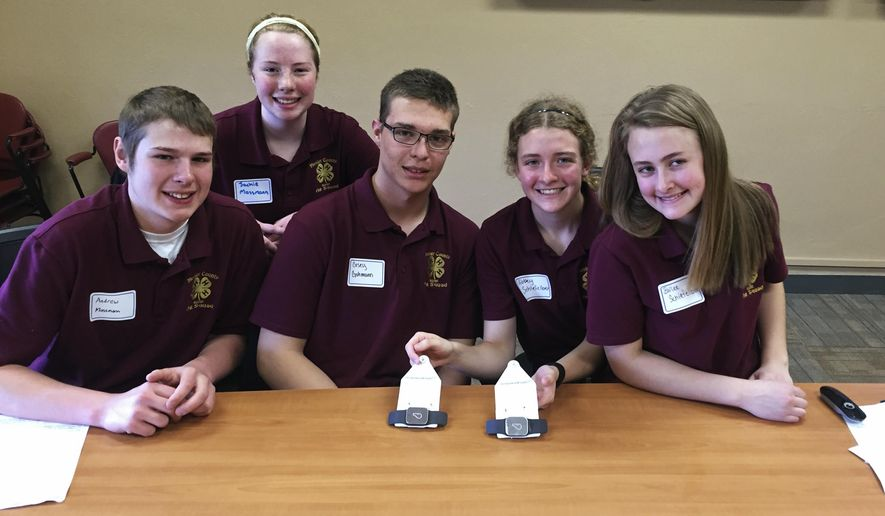 In this April 23, 2016, photo, members of the Meeker County Ag Squad are seen at the University of Minnesota in St. Paul showing off the GPS ear tags they developed to help farmers track their livestock from far away. From left are: are Andrew Massmann, Jackie Massmann, Casey Gohmann, Abbey Schiefelbein, and Bailee Schiefelbein, all of Kimball, Minn. They're taking part in the 4-H Science of Agriculture Challenge, which aims to nurture the next generation of agricultural scientists for a country facing a critical shortage of them. (AP Photo/Steve Karnowski)