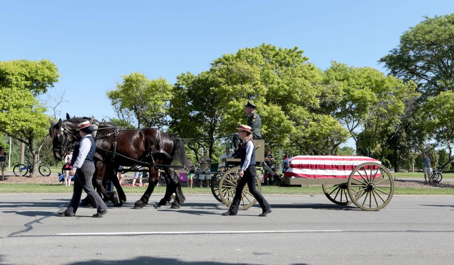 A military funeral ritual honors Richard Peter Nokell, who served in the U.S. Air Force from 1962-1966 during the Vietnam War, during the annual Memorial Day Parade on Monday, May 30, 2016, in Dearborn, Mich. (Jessica J. Trevino/Detroit Free Press via AP)  DETROIT NEWS OUT; TV OUT; MAGAZINES OUT; NO SALES; MANDATORY CREDIT DETROIT FREE PRESS