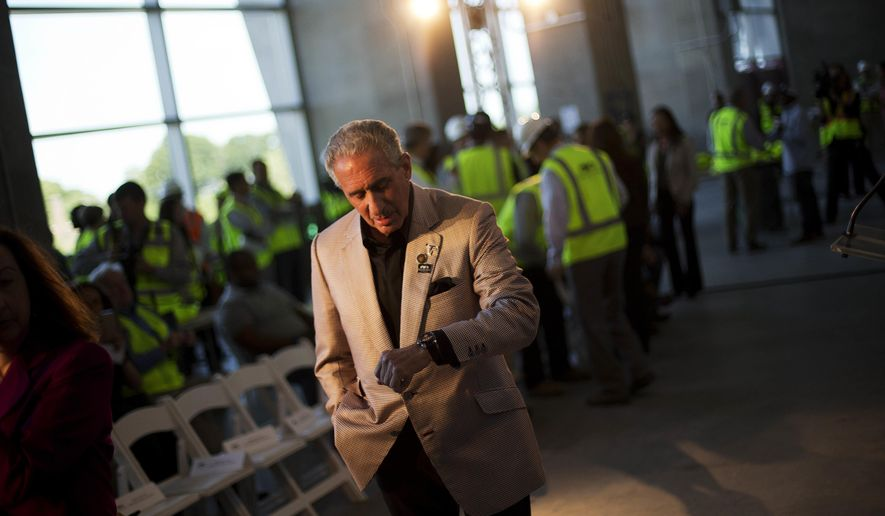 FILE - In this May 16, 2016, file photo, Atlanta Falcons owner Arthur Blank checks his watch before the start of a press event at the team's new stadium currently under construction in Atlanta. The 2019 Super Bowl is scheduled to be played at the new stadium.  (AP Photo/David Goldman, File)