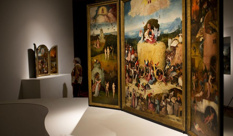 "In this Friday, May 27, 2016 photo, a man stands next to ""The Haywain"" triptych painting, right, by Dutch artist Hieronymus Bosch during an exhibition at the Prado museum in Madrid, Spain. The exhibition for the 500th anniversary of Bosch that is billed as a once-in-a-lifetime review of the best and most of the Renaissance master was inaugurated by Spain's King Felipe VI Monday May 30, 2016. (AP Photo/Francisco Seco)"