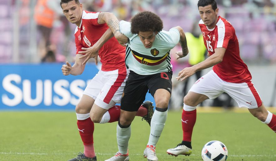 Swiss forward Granit Xhaka, left, challenges for the ball with Belgian Axel Witsel, center, next to Swiss midfielder Blerim Dzemaili, right, during a friendly soccer match between Switzerland and Belgium, at the stade de Geneve stadium, in Geneva, Switzerland, Saturday, May 28, 2016. (Jean-Christophe Bott/Keystone via AP)