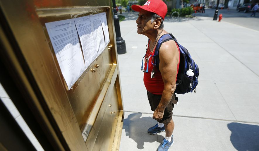 In a Friday, May 27, 2016 photo, Joe Martinez reads over information about a container outfitted with video conference electronics that is part of an art installation at Military Park in downtown Newark, N.J. The portal allows people inside a container to communicate to people in containers in other cities across the world. (AP Photo/Julio Cortez)