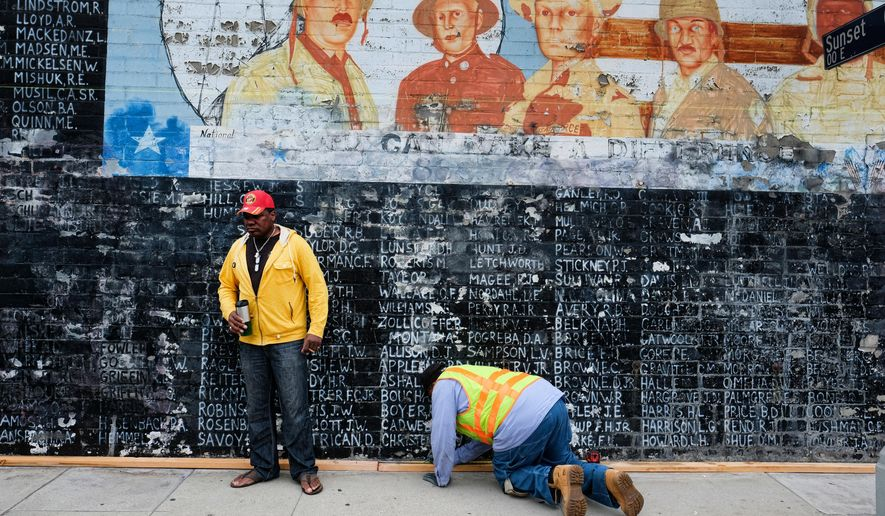 Former U.S. Marine Jon Scudder, left, watches as a Metropolitan Transit Authority worker prepares to cover a vandalized Vietnam War Memorial in the Venice area of Los Angeles on Monday, May 30, 2016. The Los Angeles memorial honoring prisoners and those missing in action during the Vietnam War has had to be covered with tarp on Memorial Day after authorities determined it was too badly damaged by graffiti to be quickly repaired. (AP Photo/Richard Vogel)