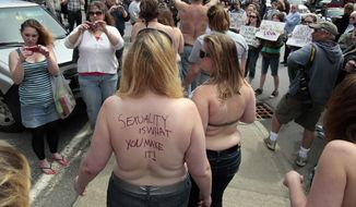 Topless protesters attract a large crowd on April 30, 2010, in Farmington, Maine. The demonstration called attention to the double-standard that it's acceptable for men, but not women, to go bare chested. (Associated Press)