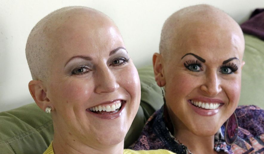 In this Thursday, May 26, 2016, photo, Annette Page, left, and her sister Sharee Page, pose for a photograph at Sharee's home during an interview, in Farmington, Utah. The two Utah sisters have received a breast cancer diagnosis within about two weeks of one another, a coincidence that doctors say is extremely rare, but gives them the chance to undergo chemotherapy together, shave each other's heads and discuss their identical symptoms. (AP Photo/Rick Bowmer)
