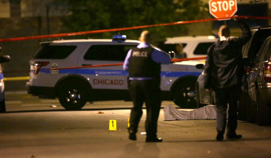 Police work the scene where a man was fatally shot in the chest in Chicago's Washington Park neighborhood on May 30, 2016. Chicago rang in the unofficial start to summer with dozens of shootings that killed several people and wounded others over Memorial Day weekend. (E. Jason Wambsgans/Chicago Tribune via AP)