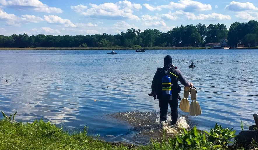 In this Monday, May 30, 2016, photo, rescue teams search for a missing 5-year-old boy in Vineyard Lake, in Brooklyn, Mich. Police said the boy died after being pulled from the lake Monday night. (Samantha Madar/MLive Media Group-Jackson Citizen Patriot via AP) LOCAL STATIONS OUT; LOCAL INTERNET OUT; MANDATORY CREDIT