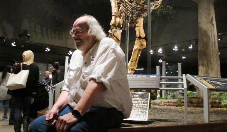 "In a Saturday, May 21, 2016 photo, Jack Horner smiles as he sits under Montana's T Rex in the Museum of the Rockies in Bozeman, Mont. The museum hosted ""Jack Horner Family Day"" ahead of Horner's retirement this summer after leading the museum for 34 years and establishing himself as one of the most famous paleontologists in the world. (AP Photo/Matt Volz)"