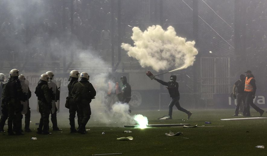 FILE - In this Saturday, Nov. 21, 2015 file photo, a Panathinaikos fan throws a fire extinguisher at policemen after the cancellation of the Greek Super League match between Panathinaikos and Olympiakos at Apostolos Nikolaides stadium in Athens. Hooliganism is making a comeback, and the timing could be bad with four high-risk matches in the first week of the European Championship in a country where the police force is already under huge strain. (AP Photo/Yorgos Karahalis, File)