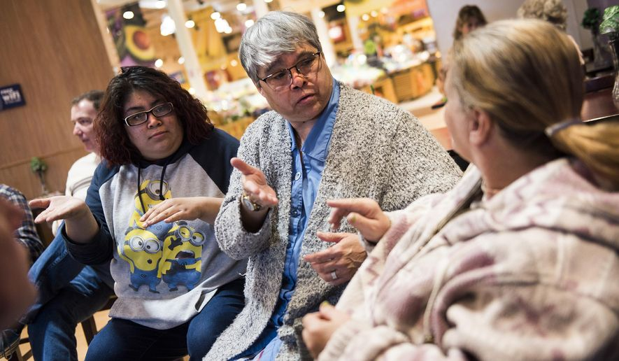 In this March 18, 2016 photo, Marta Galdamez, middle, and Celeste Solorio, left, use sign language to communicate with Vonda Altland of Hanover, Pa., right, during a monthly Hanover Deaf Chat meeting at a supermarket in Hanover, Pa. Anyone is welcome at the informal social gatherings for the deaf and hard of hearing, and those who can hear often outnumber those who are deaf, according to facilitator Jeff Wright. The get-togethers also attract American Sign Language students eager to practice what they've studied. (Shane Dunlap/The Evening Sun via AP) MANDATORY CREDIT