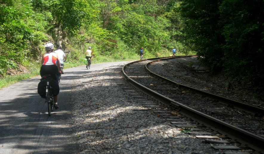 FILE - In this July 14, 2012, file photo, bicyclists finishing a three-day ride of the Great Allegheny Passage between Pittsburgh and Cumberland, Md., enter a downhill section of the trail near Cumberland, Md. As the national Rails-to-Trails Conservancy marks its 30th anniversary in 2016, Pennsylvania's rail trails, ranging from local trails a few miles long to the 150-mile Great Allegheny Passage, are among 1,970 trails nationwide that cover more than 22,300 miles. (AP Photo/Cal Woodward, File)