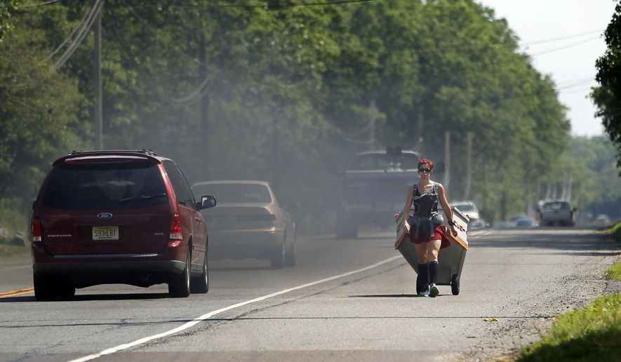 As a truck belches smoke, Greta Schwartz, of Seaville, N.J., pulls a casket as she walks along route 206, from southern New Jersey to Trenton Tuesday, May 31, 2016, in Tabernacle, N.J. Schwartz, who got the idea for the walk after attending a discussion on mental health, addiction and suicide from former U.S. Rep. Patrick Kennedy last year, hopes to arrive at the Statehouse on Wednesday. (AP Photo/Mel Evans)