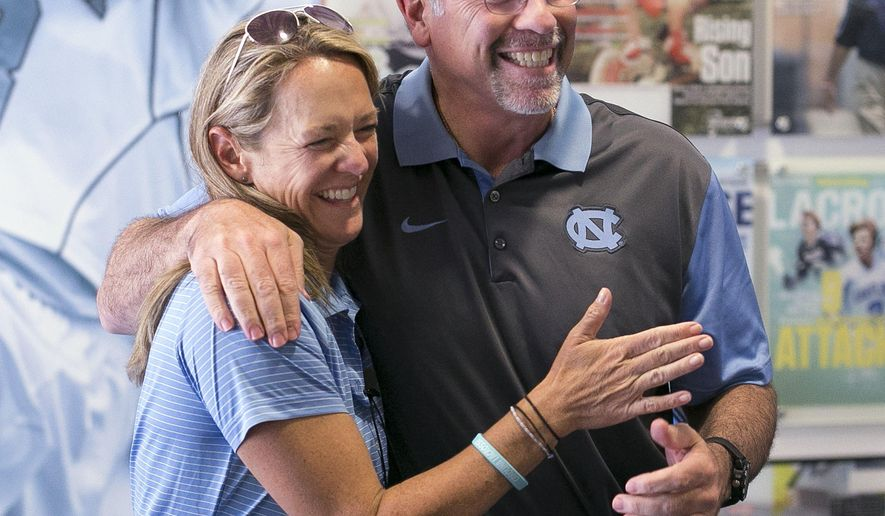 North Carolina men's lacrosse coach Joe Breschi embraces North Carolina women's lacrosse coach Jenny Levy before entering a press conference together where both coaches talked about winning dual NCAA National Championships on Tuesday, May 31, 2016 at Kenan Stadium in Chapel Hill, N.C. Both lacrosse programs defeated Maryland to win their respective titles. (Robert Willett/The News & Observer via AP)