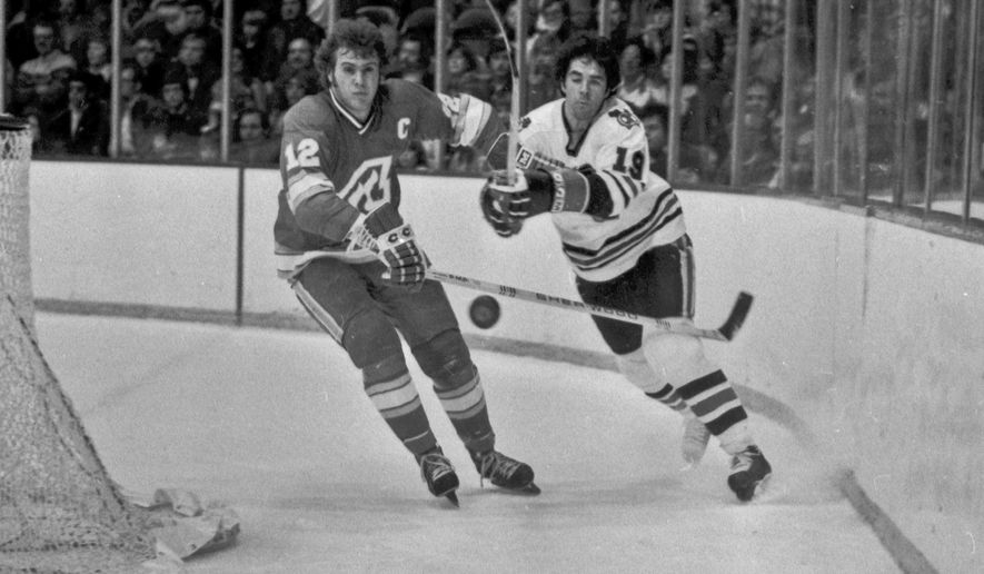 FILE - In this Dec. 18, 1977, file photo, Atlanta Flames' Tom Lysiak, left, and Chicago Blackhawks' Dale Tallon chase after the puck during the first period of an NHL hockey game in Chicago. Lysiak, a three-time NHL All-Star who played 13 NHL seasons with the Flames and Blackhawks, has died of leukemia at the age of 63. His daughter, Jessie Lysiak Braun, confirmed on Twitter that he died Monday, May 30, 2016.  (AP Photo/Fred Jewell, File)