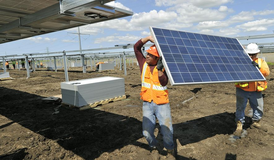 In a Tuesday, May 25, 2016 photo, Rafael Bermudes, left, and Gabriel Serano work on Lincoln Electric System's community solar project in Lincoln, Neb. What's being called Nebraska's first commercial solar energy project is expected to begin tracking the sun and delivering some of its power by June 20. (Eric Gregory/The Journal-Star via AP) LOCAL TELEVISION OUT; KOLN-TV OUT; KGIN-TV OUT; KLKN-TV OUT; MANDATORY CREDIT