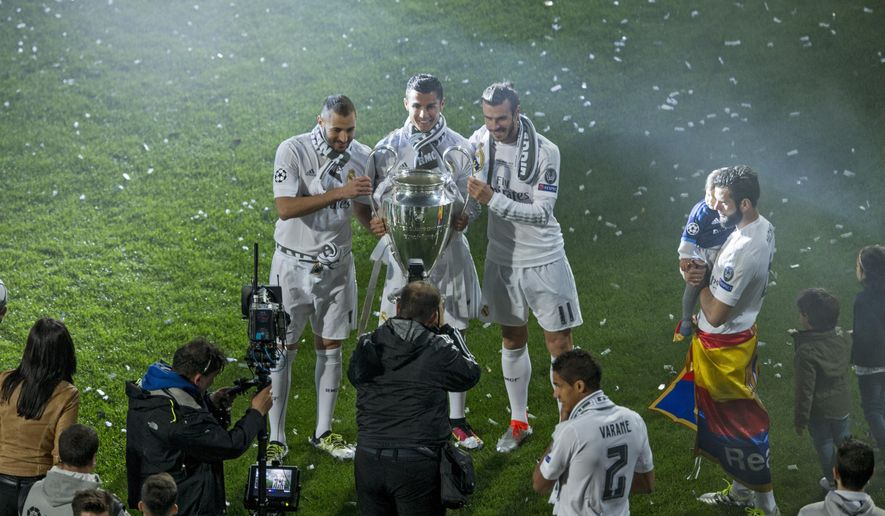 From left, Real Madrid's Karim Benzema, Cristiano Ronaldo and Gareth Bale pose for a photograph with the Champions League trophy at the Santiago Bernabeu Stadium in Madrid, Sunday, May 29, 2016. Tens of thousands of fans endured the rain to greet Real Madrid players as they returned home early Sunday from their Champions League triumph, then packed the Santiago Bernabeu Stadium at night to watch them lift the trophy one more time. (AP Photo/Francisco Seco)