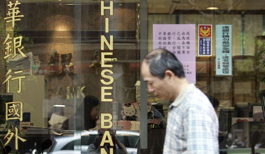 In this file photo from Jan. 16, 2007, a pedestrian passes by a branch of The Chinese Bank, a subsidiary of the financially troubled Rebar Asia Pacific Group in Taipei, Taiwan. (AP Photo/Wally Santana, File )