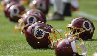 Washington Redskins helmet lie on the field before an NFL football game against the Tampa Bay Buccaneers in Landover, Md., Sunday, Oct. 25, 2015. (AP Photo/Mark Tenally)