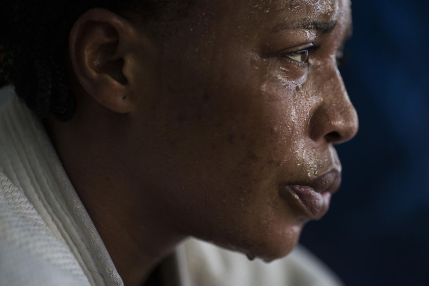 In this May 26, 2016 photo, Yolande Mabika, a refugee from the Democratic Republic of Congo, takes a break during Judo training at the Reacao Institute in Rio de Janeiro, Brazil, as she trains in hopes of making the cut for the first Olympic team of refugee athletes. In 2013, Mabika and another judo athlete from Congo traveled to Brazil with the team to compete at the World Judo Championships. They say officials left them at their downtown Rio hotel for three days prior to the competition without food, money or passports. (AP Photo/Felipe Dana)