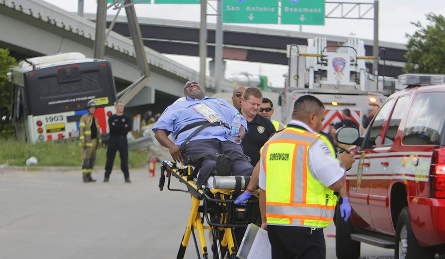 A Metro operator who was riding as a passenger on a Metro bus involved in a crash is removed by emergency workers, Wednesday, June 1, 2016, in Houston. A Houston transit bus hit a pickup truck and slammed into an overhead highway sign, injuring dozens of people. (Mark Mulligan/Houston Chronicle via AP) MANDATORY CREDIT