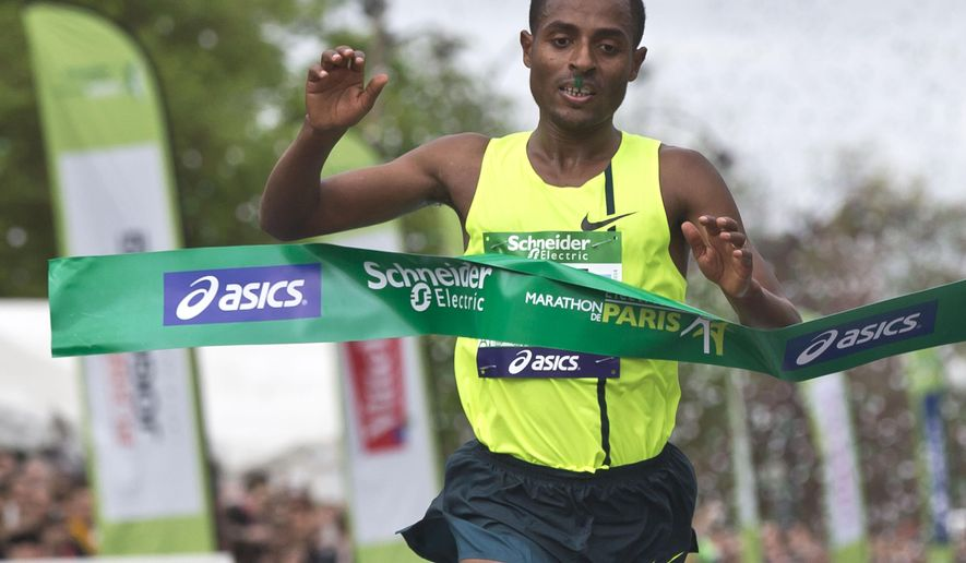 "FILE- In this Sunday, April 6, 2014 file photo, Ethiopia's runner Kenenisa Bekele crosses the finish line to win the 38th Paris Marathon,  in Paris. Bekele says his exclusion from Ethiopia's marathon team for the Olympics is ""unjust"" and has called the selection criteria the national federation used ""biased"".(AP Photo/Michel Euler, File)"