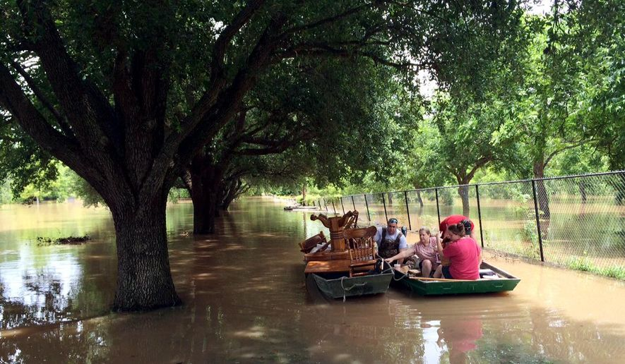 Dustin Toll, left, and other family members use two boats on Wednesday, June 1, 2016, to remove furniture from the mobile home of his grandparents, which had been flooded by the Brazos River in Rosenberg, Texas. (AP Photo/Juan Lozano)