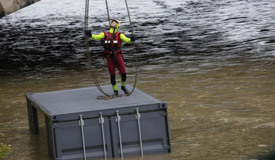 A Paris fireman anchors a flooded container used by a restaurant on the river Seine in Paris, Wednesday, June 1, 2016. The Seine River has overflowed embankments in Paris as floods hit or threaten cities and towns around France.(AP Photo/Jerome Delay)