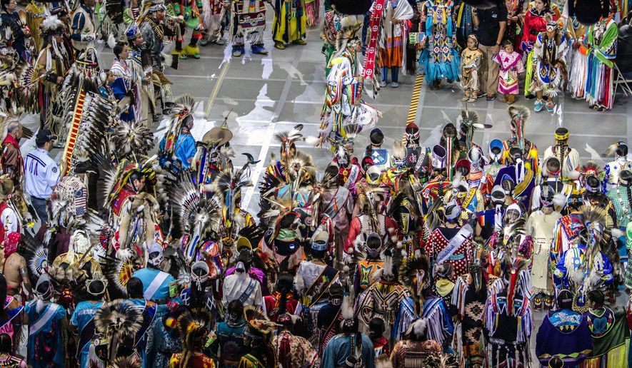 FILE - In this April 25, 2015, file photo, Native American and indigenous dancers surround head man dancer, Juaquin Hamilton, from Shawnee, Okla., following the grand entrance of the annual Gathering of Nations in Albuquerque N.M. One of North America's largest powwows has announced Wednesday, June 1, 2016, the event will move to a smaller venue in New Mexico. (AP Photo/Mark Holm, File)