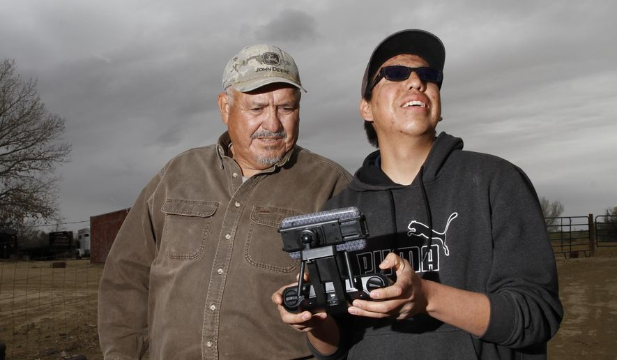 In this April 8, 2016 photo, Gary Clark watches his grandson Jayvion Chee fly a drone, at Clark's farm in Shiprock, N.M. (Jon Austria /The Daily Times via AP) MANDATORY CREDIT