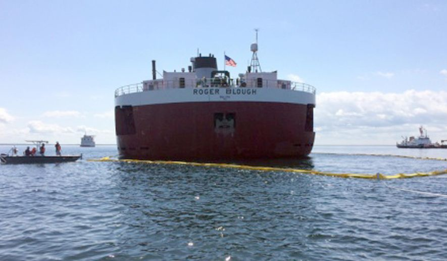 In this May 30, 2016 photo provided by the United States Coast Guard, responders place a protective boom around the stern of the motor vessel Roger Blough, that ran aground near Gros Cap Reefs Light in Lake Superior on May 27. The Coast Guard is working on plans on how it will try to free the freighter in Whitefish Bay off Michigan's Upper Peninsula. (Lt. Cmdr. Merridith Morrison/ United States Coast Guard via AP)