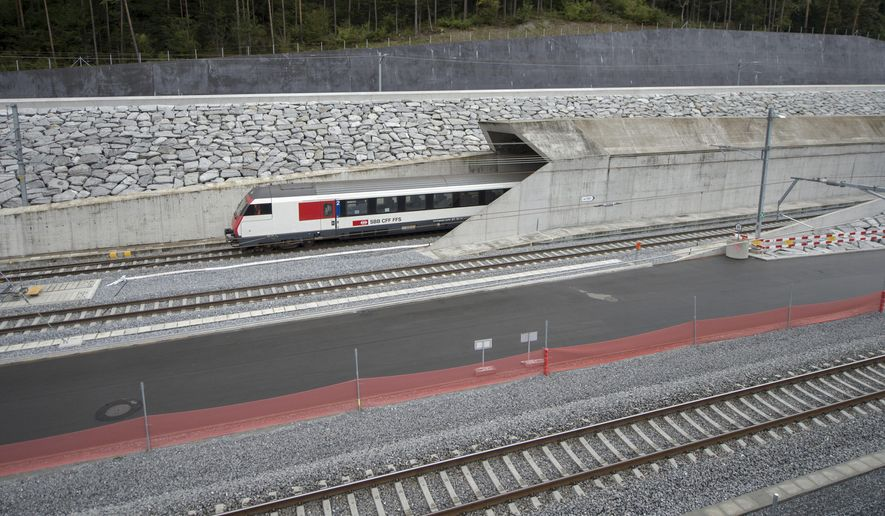 FILE - In this Oct. 8, 2015 file photo a test train drives close to the northern gate near Erstfeld, Switzerland. The celebrations of the opening of the Gotthard  Base Tunnel  will start on June 1, 2016. With a length of 57 km (35 miles) crossing the Alps, the Gotthard Base tunnel is the  world's longest train tunnel. (Urs Flueeler/Keystone via AP, file)