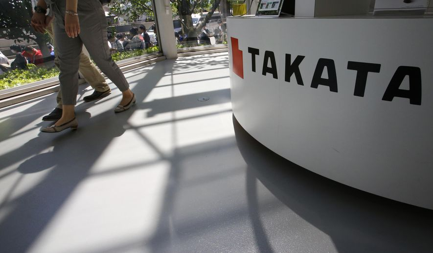 FILE - In this May 4, 2016, file photo, visitors walk by a Takata Corp. desk at an automaker's showroom in Tokyo. A U.S. Senate report says at least four automakers are selling new vehicles that have potentially deadly Takata air bag inflators. The report by Commerce Committee Democrats says some 2016 and 2017 models from Fiat Chrysler, Mitsubishi, Toyota and Volkswagen have a type of inflator that is prone to rupture and presents a potential danger to drivers and passengers. (AP Photo/Shizuo Kambayashi, File)