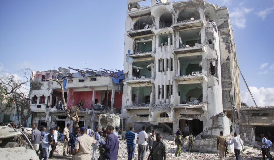 Security forces examine the scene after a bomb attack on Ambassador Hotel in Mogadishu, Somalia, Thursday, June 2, 2016. Somalia's Islamic extremist rebels, al-Shabab, stormed the hotel, often frequented by government officials and business executives, killing people and taking a number of hostages, police said. (AP Photo/Farah Abdi Warsameh)