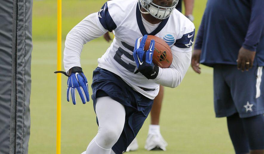 Dallas Cowboys running back Ezekiel Elliott runs through drills during an NFL football training camp, Wednesday, June 1, 2016, in Irving, Texas. (AP Photo/Tony Gutierrez)