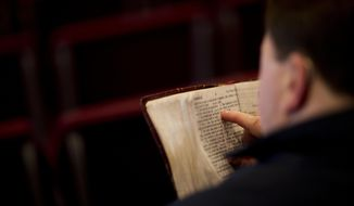 In this Sunday April 10, 2016, file photo, a parishioner reads the bible before a service at the Christian Fellowship Church in Benton, Ky. (AP Photo/David Goldman) ** FILE **